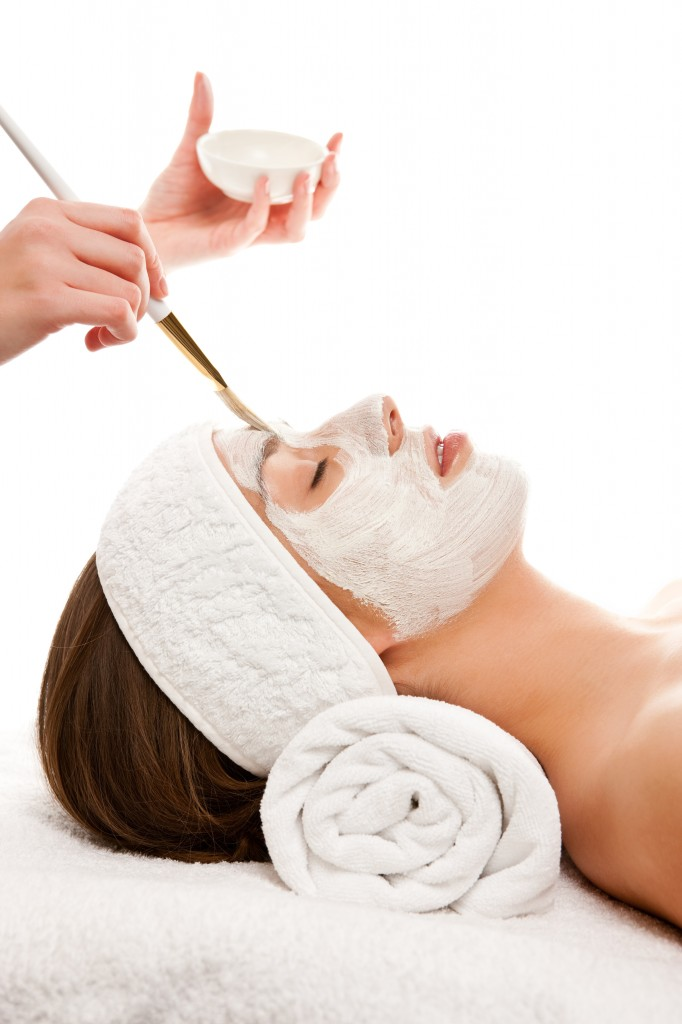 Woman receiving facial mask while lying on white towels